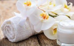 润湿的奶油和兰花在木背景 免版税图库摄影