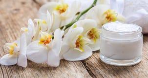 润湿的奶油和兰花在木背景 库存照片