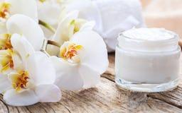 润湿的奶油和兰花在木背景 免版税库存照片