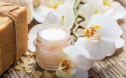 润湿的奶油和兰花在木背景 库存图片