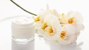 润湿的奶油和兰花在白色背景 免版税库存照片