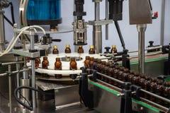 液体填装的和加盖的瓶机器 免版税库存图片
