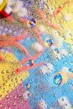 液体水抽象五颜六色的背景滴在色的backgdrop反射图片前面的 免版税库存照片