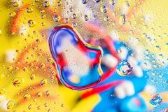 液体水抽象五颜六色的背景滴在色的backgdrop反射图片前面的 免版税库存图片