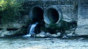 液体流出落在从污水的自然河水用管道输送 免版税库存图片