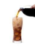 液体涌入与在白色后面隔绝的冰的一块玻璃 免版税库存图片