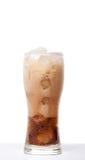 液体涌入与在白色b隔绝的冰的一块玻璃 免版税库存图片