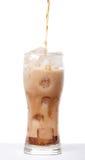 液体涌入与在白色b隔绝的冰的一块玻璃 图库摄影