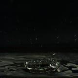 水滴液体,被形成一个黑暗的火山口和飞溅 库存照片