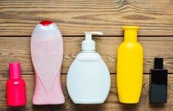淋浴的产品在瓶和瓶香水在一张木桌上 私有的关心 卫生学和秀丽的对象 顶视图 免版税库存照片