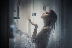 淋浴通过浴屏幕的妇女的未聚焦的画象与一点下落 安心和放松在长的紧张天以后 免版税库存照片
