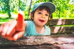 淘气鬼儿童在照相机嘲笑画象自然b的点手指 库存照片