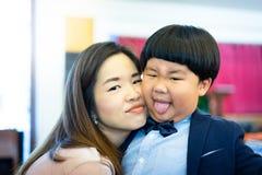 淘气鬼和他的母亲充当有正式的教会 免版税库存照片
