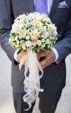 淡粉红和黄色花和丝带婚礼花束在新郎的手上 免版税库存照片