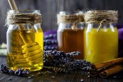 淡紫色和草本蜂蜜在玻璃瓶子有蜂蜜匙子的在黑暗的木背景 库存照片
