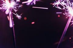 淡紫色孟加拉闪烁发光物在黑背景点燃以纪念圣诞节新年和生日庆祝 免版税库存照片