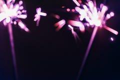 淡紫色孟加拉闪烁发光物在黑背景点燃以纪念圣诞节新年和生日庆祝 库存照片