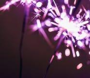 淡紫色孟加拉闪烁发光物在黑背景点燃以纪念圣诞节新年和生日庆祝 免版税库存图片