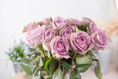 淡紫色庭院上升了 玫瑰花束花在玻璃花瓶的 破旧的别致的家庭装饰 接近的露水小滴放牧叶子早晨理想的水 库存照片