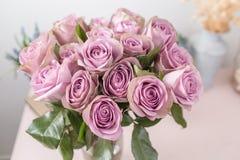 淡紫色庭院上升了 玫瑰花束花在玻璃花瓶的 破旧的别致的家庭装饰 接近的露水小滴放牧叶子早晨理想的水 免版税库存照片