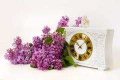 淡紫色开花、老手表和天使雕塑 免版税库存照片