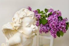 淡紫色开花和天使雕塑浪漫静物画在白色的 免版税库存图片