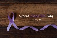 淡紫色癌症的所有类型的丝带标志在木桌上的 图库摄影