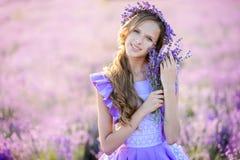 淡紫色的领域的美丽的女孩在日落的 免版税库存图片