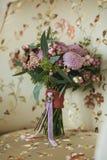 淡紫色美丽的婚礼花束用莓果,站立在有天花板的一把白色扶手椅子 库存照片