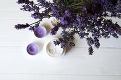 淡紫色花、蜡烛和奶油在白色木背景 图库摄影