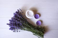 淡紫色花、蜡烛和奶油在白色木背景 库存图片