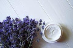 淡紫色花、蜡烛和奶油在白色木背景 库存照片