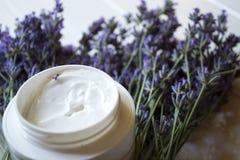 淡紫色花、蜡烛和奶油在白色木背景 免版税图库摄影