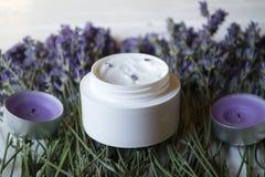 淡紫色花、蜡烛和奶油在白色木背景 免版税库存图片