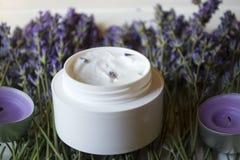 淡紫色花、蜡烛和奶油在白色木背景 免版税库存照片