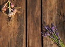 淡紫色花和大蒜在老木背景 图库摄影