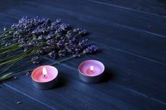 淡紫色花和灼烧的蜡烛在深蓝木背景 库存图片
