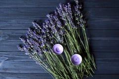 淡紫色花和紫罗兰色蜡烛在一张深蓝木桌上 库存图片