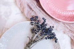 淡紫色花束在有一个样式的一块美丽的陶瓷桃红色和灰色板材开花与纱布料 特写镜头 免版税库存图片