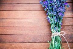 淡紫色花束的顶视图放置了在棕色木背景 复制空间 免版税库存照片