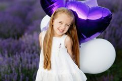 淡紫色领域的愉快的逗人喜爱的小女孩与紫色气球 查出的黑色概念自由 库存图片