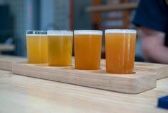 淡色的工艺啤酒飞行坐在a的木板条 免版税库存图片
