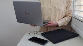 淡色的正式衬衣的一个人在角落站立在窗口附近 库存照片