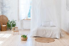 淡色的舒适卧室与一个木地板、一张大有四根帐杆的卧床床、花藤椅和篮子  斯堪的纳维亚simpli 图库摄影