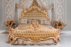 淡色的豪华卧室与金黄家具细节 在典雅的经典之作的大舒适的双重皇家床 库存照片
