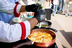 淡菜和海鲜由一个金属盘子的厨师准备了在公司酒酱汁、草本和香料 库存照片
