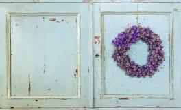 淡紫色垂悬在一个老门的花花圈 免版税库存图片