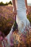 淡紫色婚礼花束在新娘手上 免版税库存图片