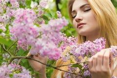 淡紫色开花的树的美丽的逗人喜爱的性感的女孩在夏天温暖的天 免版税库存照片