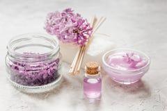 淡紫色自然化妆用品为温泉设置了有盐石头桌背景 免版税库存图片